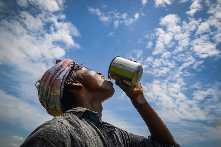 Man wearing a turban drinks water with the bright cloudy sky above him on a hot summer day