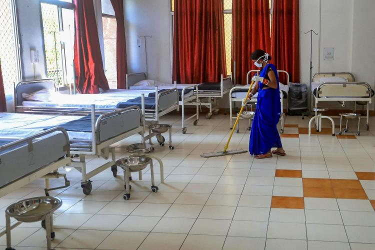 A woman cleaner mopping the floor of a hospital