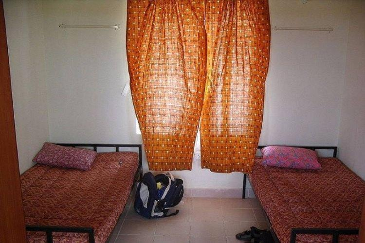 Representational image of a hostel room shows two beds on either side of the room and a window with curtains in the middle