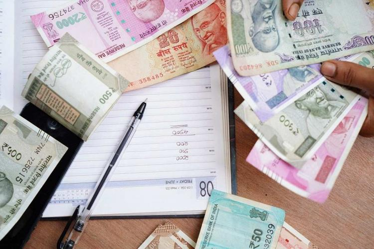 Money is seen strewn around a notebook and a pen A pair of hands is seen counting a wad of notes