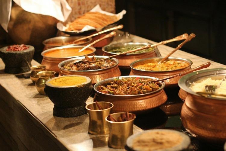 copper vessals holding curries naan and rice at an indian food buffet