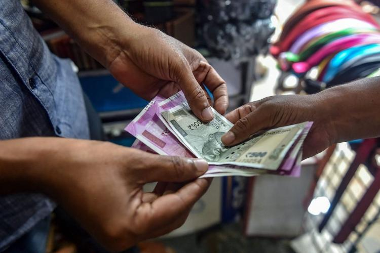 A mans hands hold on to Rs 100 and Rs 2000 notes