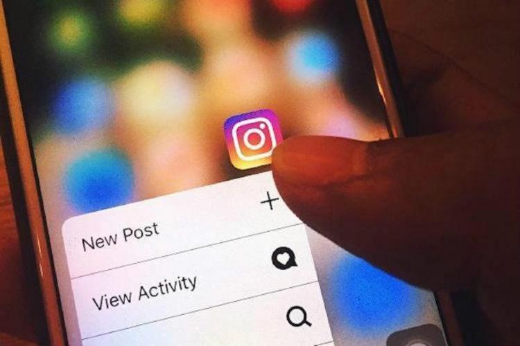 Person clicking on the Instagram app on a phone