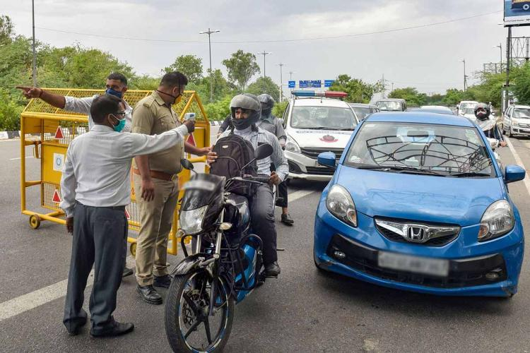 Officials are seen guiding cars and bikes in the picture Yellow metal barricades are set up A blue car is seen moving along as a man on bike is seen being guided by an official in plain clothes along with a police official