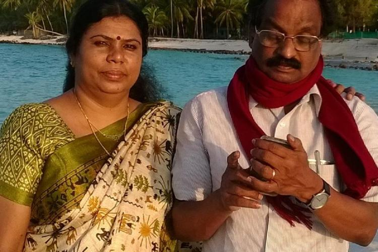 PK Jameela and AK Balan stand side by side while he looks down at a phone