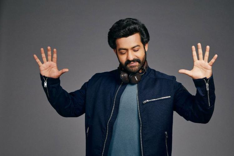 Jr NTR in a grey shirt and black jacket with headphones on and eyes close palms raised
