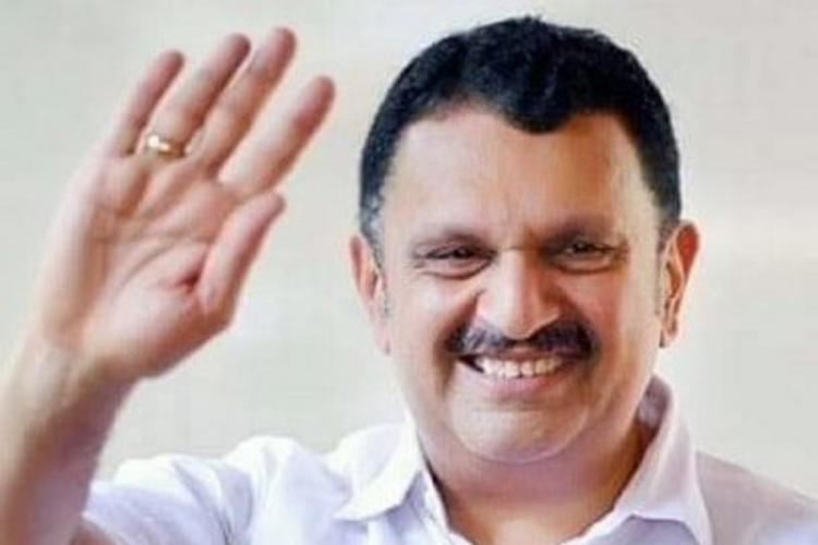 Middle-aged politician wearing white and smiling waves with his right hand