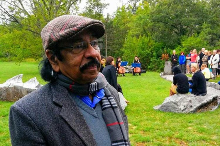 Middle-aged man stands sideways wearing shirt and coat and spectacles and a cap on his head as in the lush background you see other people in a picnic mood
