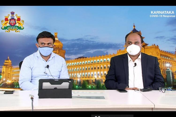 Karnataka Minister K Sudhakar at a video press conference Behind him is a screen with a picture of the vidhana soudha and with him is another official Both men are wearing face masks