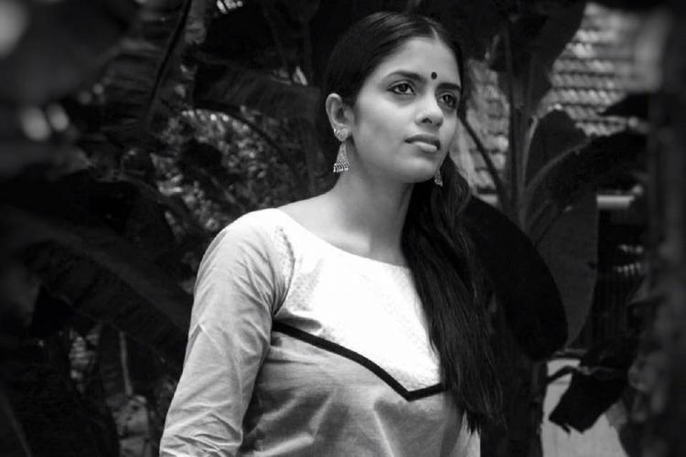 Black and white photo of Kani in a kurthi wearing a bindi and her long straight her tied and thrown to one side
