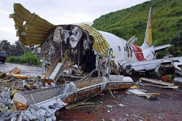 The split open part of the plane and its remaining half spilling contents onto the ground The photo is taken in the day and in the background you can see green bushes