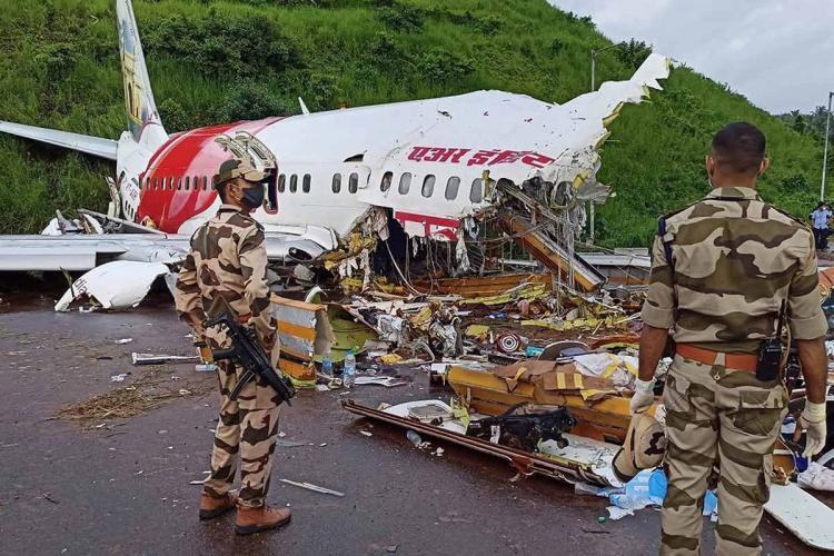 Two security personnel stand before the wreckage of the Dubai-Kozhikode Air India Express flight that crashed at Karipur airport on August 7, 2020