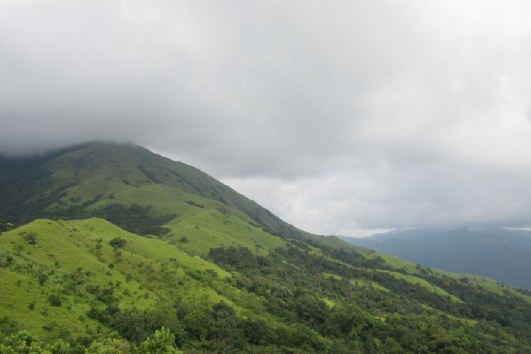 clouds hover over a green hill in karnataka ghats