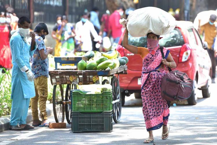 woman holding a sack on her head and luggage walks home after migrant labourer trains were cancelled fruit vendors watch her go bengaluru