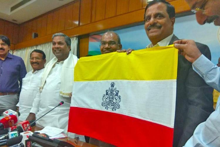 Former CM Siddaramaiah launching the flag in 2018 with officials holding it up to reveal yellow white and red with states symbol in between