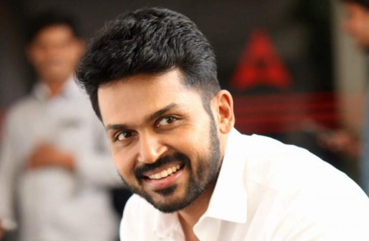 Hero Karthi posing for a picture in a white shirt