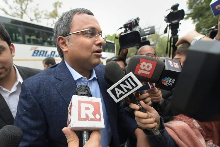 Karti Chidambaram wearing a coat speaking to media in front of him are seen television mikes