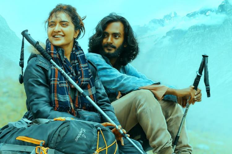 A female and a male trekker sit by the mountains sticks in hands smiling