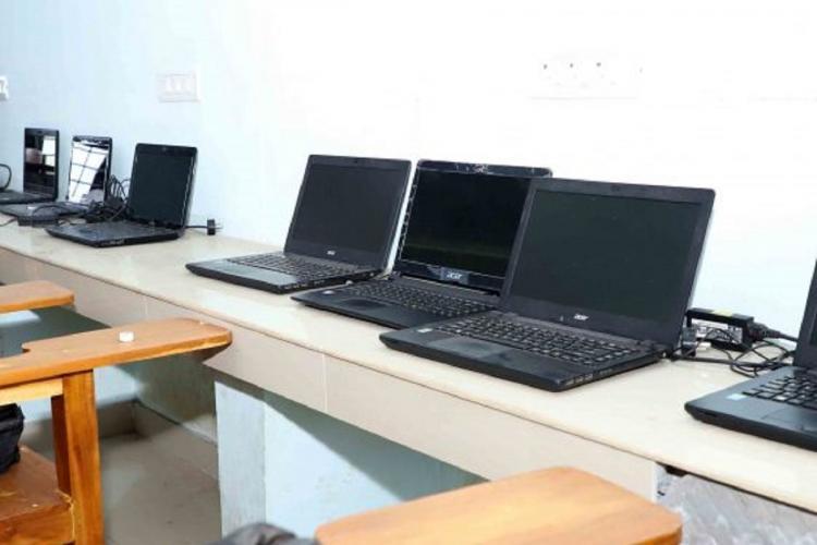 A few laptops kept on a long built in desk