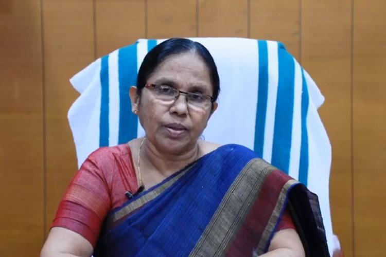 KK Shailaja teacher in office in a deep blue and red saree