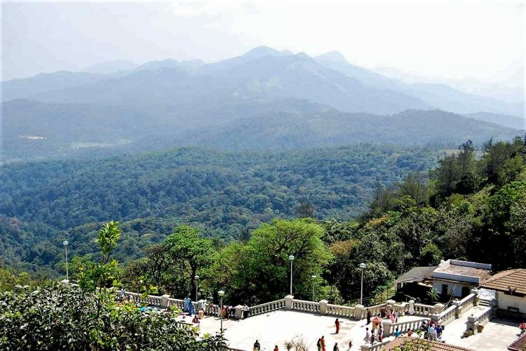 Taken from the hill where the Talacauvery temple is located in Kodagu the photo shows a large terrace overlooking a forested valley and mountains in the distance Some people can be seen walking about in the terrace