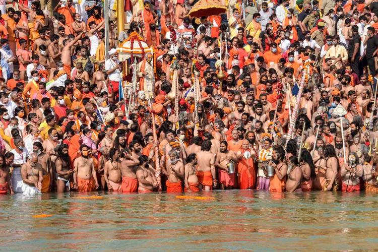Scores of participants of Kumbh Mela taking dip in water without abiding COVID-19 protocol