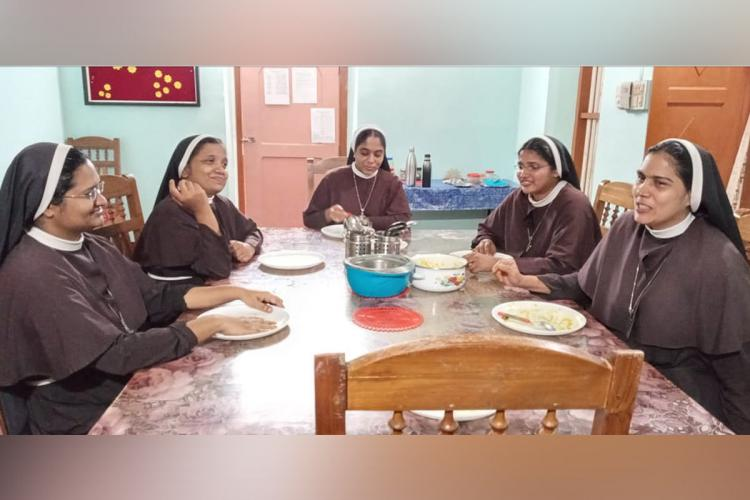 The five nuns from the Missionaries of Jesus MJ congregation from the St Francis Mission Home Kuravilangad in Keralas Kottayam district They are sitting around a dining table talking and having a meal