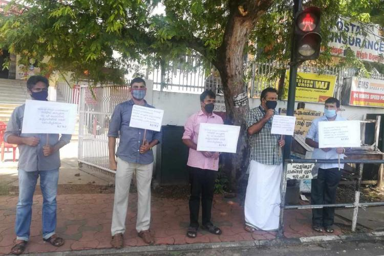 Five men stand with placards at 1 metre apart in front a tree by the side of the road