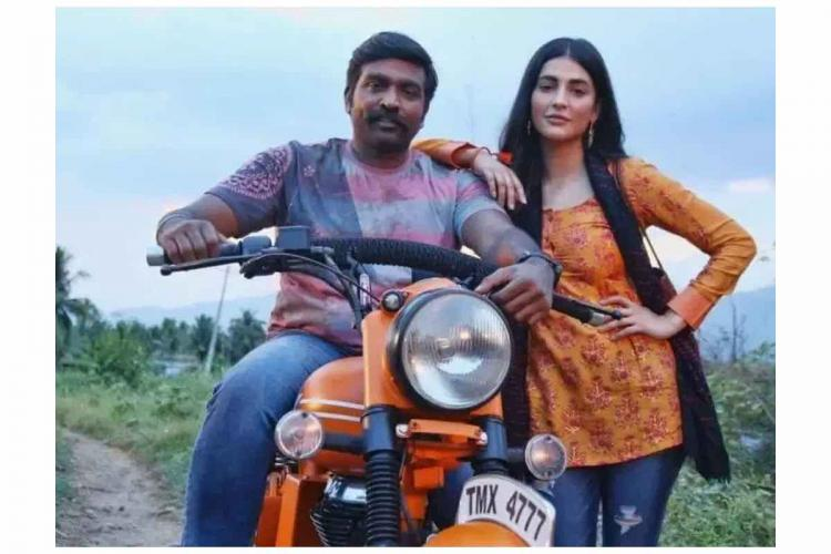 Vijay Sethupathi and Shruti Haasan in Laabam where the former is seen on a bike and the latter standing next to him