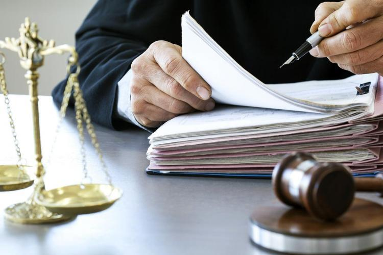 A lawyer, holding a pen and going through a file. Gavel and scales of justice are also seen on the table.