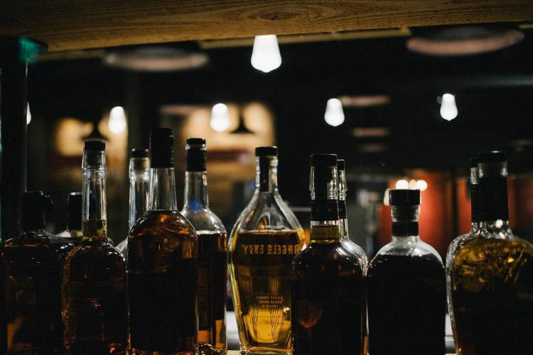 A few liqour bottles are lept on a bar table in dim light