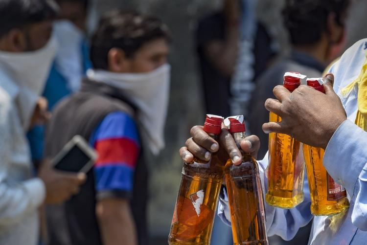 Man holding liquor bottles purchased during the coronavirus lockdown in India
