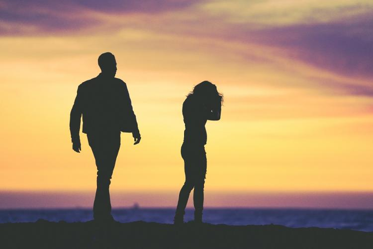 Silhouette of a man and woman against a sunset sky of yellow and purple The couple look like they are upset and the woman while standing has her hands in her hair and the man looks at her and is about to approach her