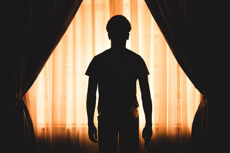 Silhouette man standing in front of curtains