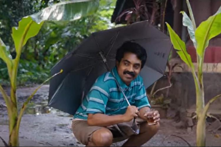 Man wearing blue t shirt and lungi sits down next to two banana plants with an umbrella in the rain