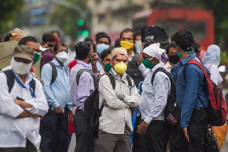 Men wearing masks wait for a bus in Mumbai