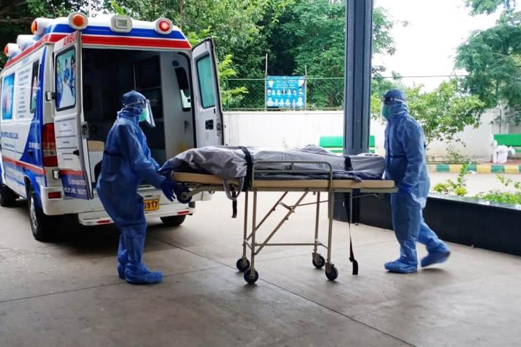 People in PPE roll a body into a waiting ambulance