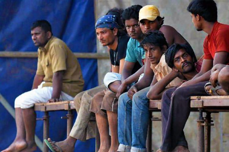 Labourers in India sit in a row