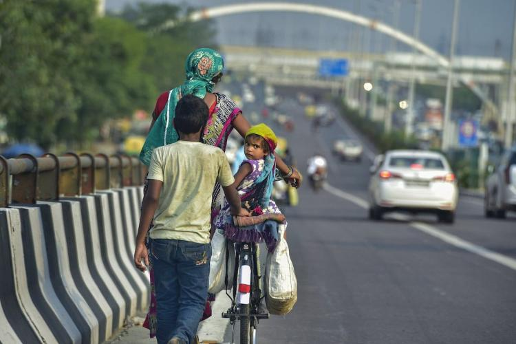 A woman in a saree and scarf covering her head is pushing a bicycle on a wide city road with traffic seen in the background Her back is to the camera A little girl in a purple and white dress and a scarf on her head is seated on the cycle and looks back at the camera A man in jeans and white t-shirt with his back to the camera is seen walking behind the bicycle