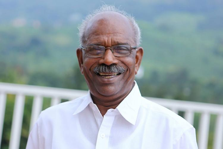 MM Mani in white shirt smiles at the camera. He has a pair of specs and behind him are hills far in the background