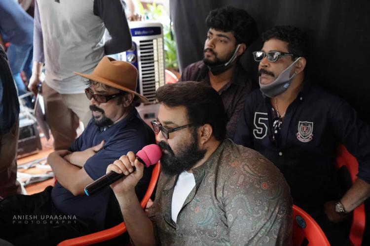 Mohanlal on the first day of shooting of his directorial debut Barroz seated and speaking into a mic Seen with him are cinematographer Santosh Sivan and producer Antony Perumbavoor