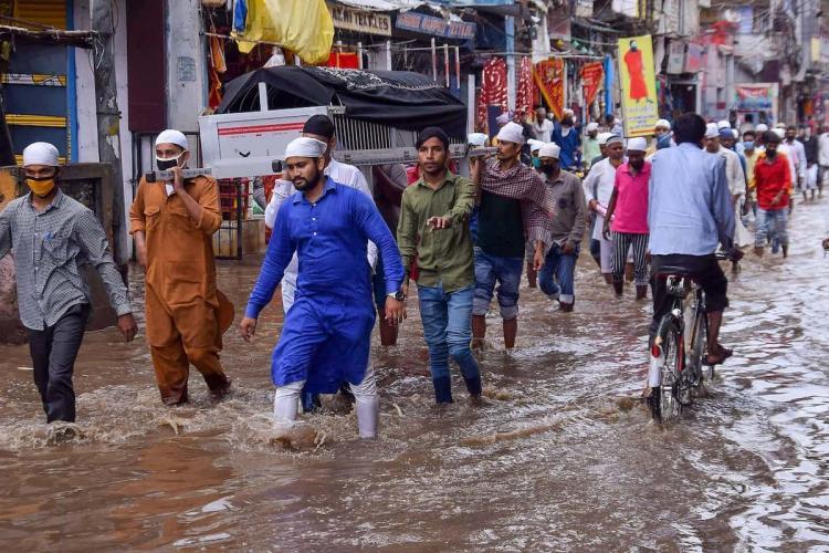 People wade through rainwater