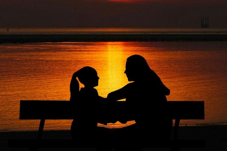 Silhouette of adult and child talking in front of a water body