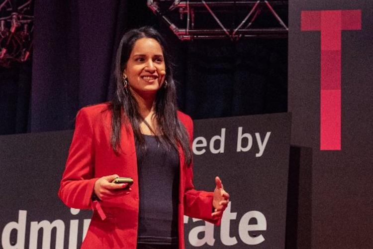 Nandini Jammi co-founder of Sleeping Giants and co-founder of Check My Ads wearing a red jacket and speaking at an event