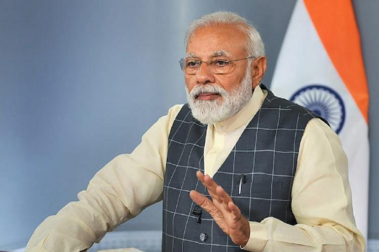 Indian Prime Minister Narendra Modi stands sideways wearing a half sleeved jacket one of his arms raised in mid-speech Behind him an Indian national flag is seen