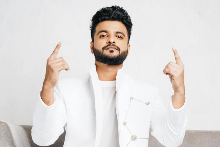 Neeraj Madhav in white with hands raised