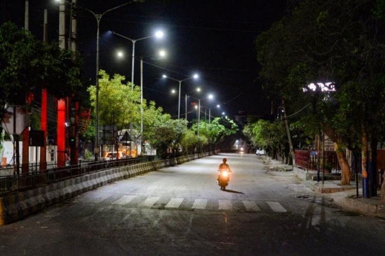 A man riding a motorcycle on a deserted road at night