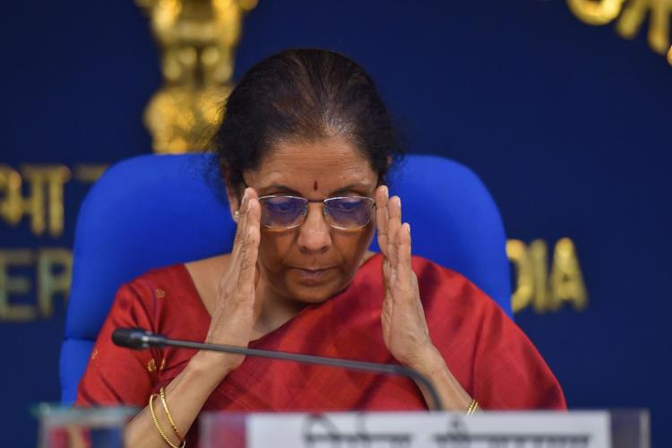 Finance Minister Nirmala Sitharaman in a red sari adjusting her glasses and looking serious