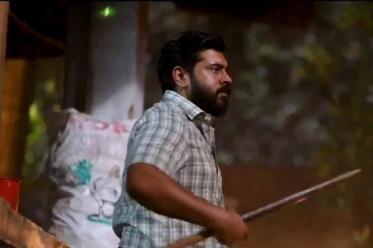 Bearded Nivin wears a white check shirt and looks sideways with an iron rod in his hand