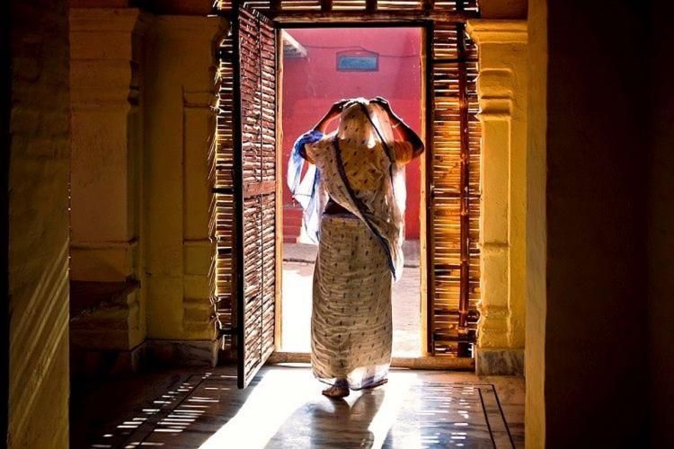 A representative picture of an old woman standing on the entrance of her home adjusting her veil